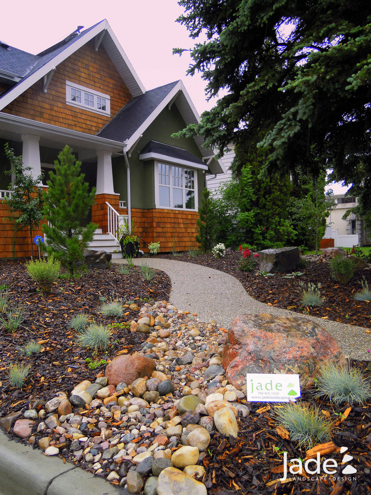 A collection of different colored rocks makes a stunning front-yard feature. Via Jade Landscaping
